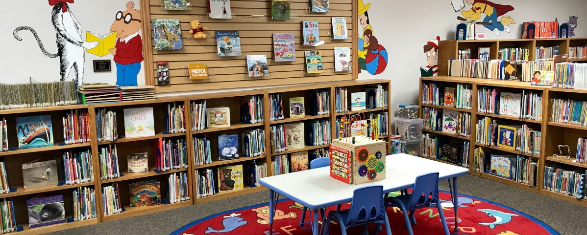 Library shelves filled with books and a children's table